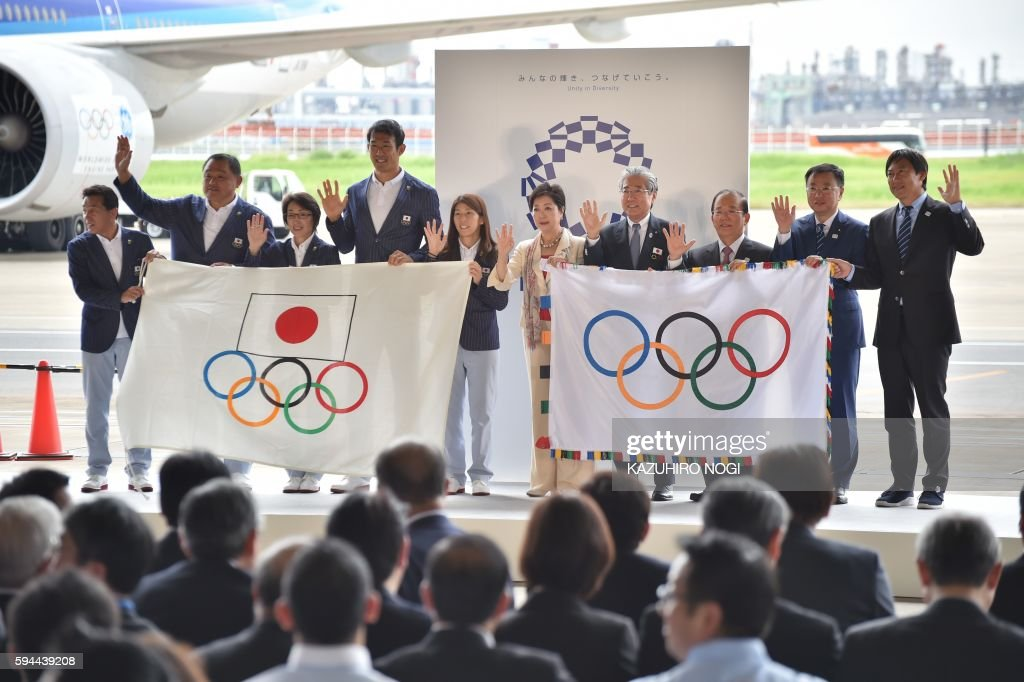 Tokyo governor Yuriko Koike (5th R), Japan Olympic Committee officials and their Rio de Janeiro Olympic squad leaders pose with flags during the offical flag arrival ceremony at the Tokyo's Haneda airport on August 24, 2016. The Olympic flag arrived in Tokyo on August 24, as Japan's capital gears up to host the 2020 Games, with officials promising smooth sailing after Rio's sometimes shaky 2016 instalment. / AFP / KAZUHIRO