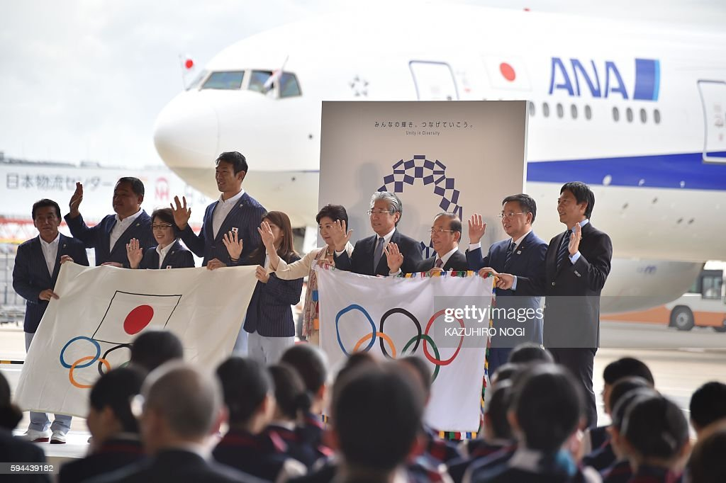 Tokyo governor Yuriko Koike (C), Japan's Olympic Committee officials and Rio de Janeiro Olympic squad leaders pose with flags during the official flag arrival ceremony at the Tokyo's Haneda airport on August 24, 2016. The Olympic flag arrived in Tokyo on August 24, as Japan's capital gears up to host the 2020 Games, with officials promising smooth sailing after Rio's sometimes shaky 2016 instalment. / AFP / KAZUHIRO