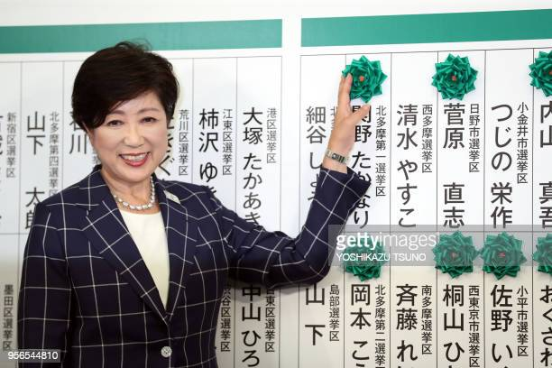 Tokyo Governor Yuriko Koike puts a rosette on a candidate name of her party 'Tomin First no Kai' at the Tokyo Metropolitan Assembly election in Tokyo...