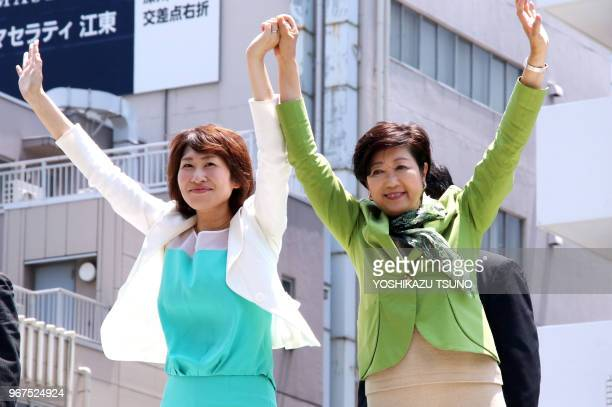 Tokyo Governor Yuriko Koike raises hands with her party 'Tomin First no Kai' candidate as she delivers a campaign speech for the upcoming Tokyo...