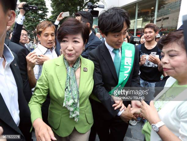 Tokyo Governor Yuriko Koike shakes hands with a supporter of her party 'Tomin First no Kai' candidate after she delivered a campaign speech for the...