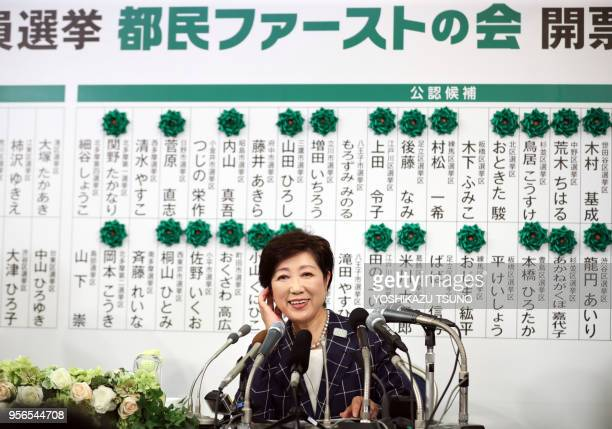 Tokyo Governor Yuriko Koike smiles as she puts a rosette on a candidate name of her party 'Tomin First no Kai' at the Tokyo Metropolitan Assembly...