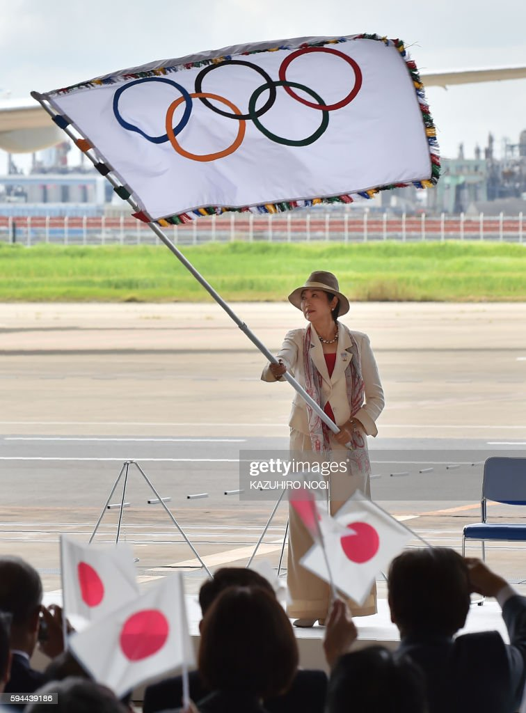 Tokyo governor Yuriko Koike waves the Olympic flag during its arrival ceremony at the Tokyo's Haneda airport on August 24, 2016. The Olympic flag arrived in Tokyo on August 24, as Japan's capital gears up to host the 2020 Games, with officials promising smooth sailing after Rio's sometimes shaky 2016 instalment. / AFP / KAZUHIRO