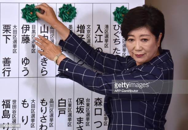 Tokyo Governor Yuriko Koike who is the current leader of the newlyformed Tomin First no Kai party marks the names of candidates who won a seat in the...