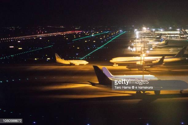 Tokyo Haneda International Airport (HND) in Japan night time aerial view from airplane