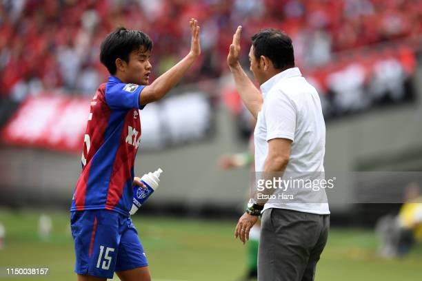 Tokyo head coach Kenta Hasegawa and Takefusa Kubo shake hands during the J.League J1 match between FC Tokyo and Consadole Sapporo at Ajinomoto...