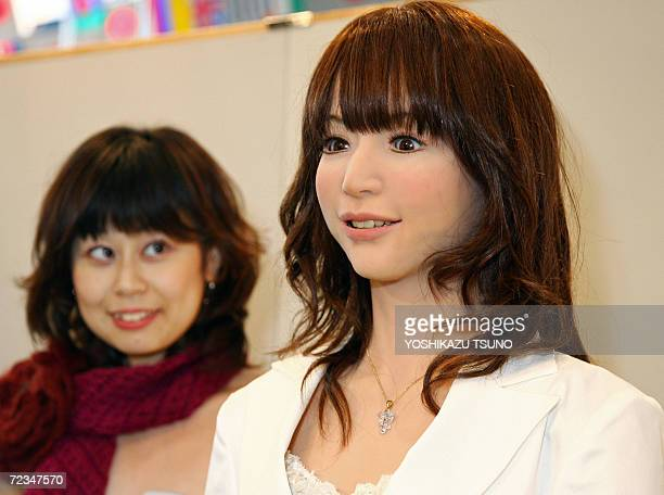 A 165m tall humanoid robot 'Actroid DER2' produced by Japanese robotic venture Kokoro smiles while singer Akiko Matsuide a member of robot and human...