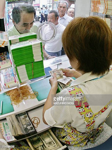 A clerk counts bank notes of a customer buying lottery tickets for the 300 million yen Summer Jumbo Lottery at a Tokyo ticket booth 13 July 2006...