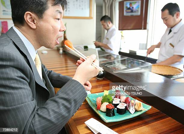 Customer eats sushi at a Tokyo sushi bar, 20 December 2006. Whether it?s sushi topped with foie gras or wrapped around cream cheese, Japanese...