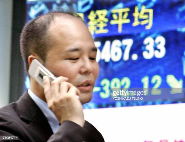 A Japanese businessman uses his mobile phone as he walks past a share price board in downtown Tokyo 31 May 2006 Japanese share prices dropped 39212...