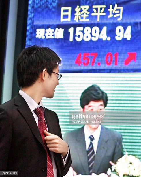 A man walks in front of a share prices board in downtwon Tokyo 21 February 2006 Japanese share prices closed up almost three percent 21 February...