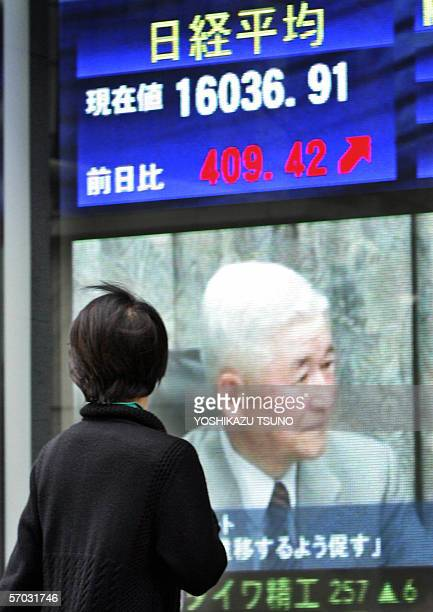 Pedestrian gazes at a share prices board showing governor Bank of Japan Toshihiko Fukui in Tokyo,+ 09 March 2006. Japanese share prices rose 409.42...