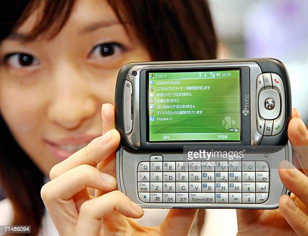 An employee of Japan's mobile communication giant NTT DoCoMo displays the new PDA shaped mobile handset htc Z produced by Taiwanese maker HighTech...