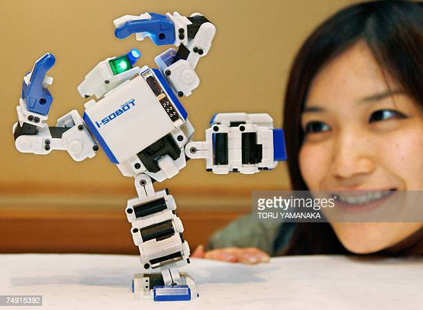 An employee of Japan's Takara Tomy introduces the world's smallest remotecontrolled humanoid robot iSobot during a press preview for the fourday...