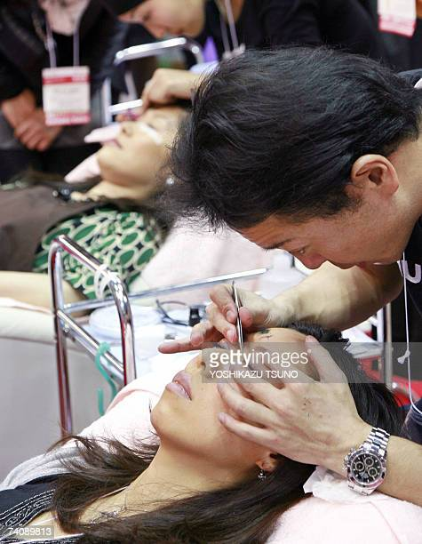 An esthetician transplants artificial eyelashes to a guest during a demonstration at the 'Beautyworld Japan' beauty service and products trade show...