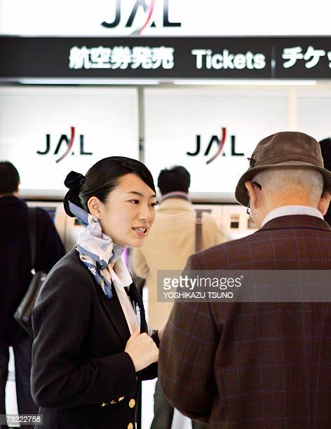 Asia's largest air carrier Japan Airlines ground staff advices how to use automatic ticketing machines at Tokyo's Haneda Airport 06 February 2007 JAL...