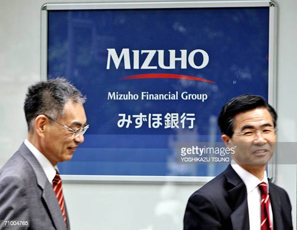 Businessmen pass before a branch of Japan's mega bank Mizuho Bank in Tokyo 22 May 2006 Mizuho Financial Group Japan's secondbiggest bank reported a...