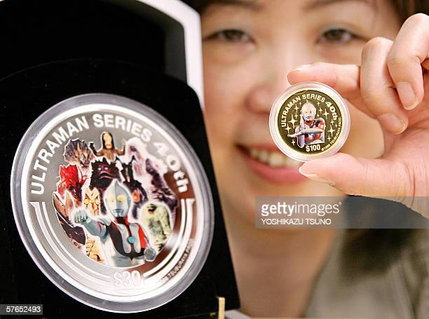 Chikako Kubo of Japanse money commodity trader Taisei displays an ounce Tsubaruan gold coin and onekilogram silver coin designed after the popular...