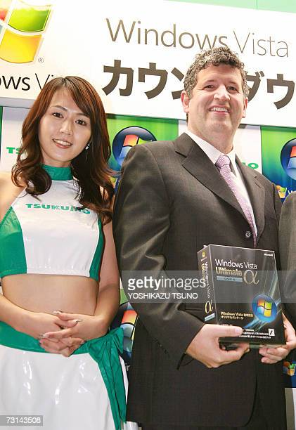 Darren Huston President of US software giant Microsoft's Japanese subsidiary smiles as he holds a package of Microsoft's new operating system Windows...
