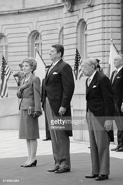 Emperor Hirohito President Reagan and Mrs Reagan listen to the national anthem during welcoming ceremonies at Akasaka Palace
