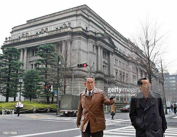 Japanese businessmen walk before the headquarters of the Bank of Japan in Tokyo 17 January 2007 The Bank of Japan is unlikely to raise interest rates...