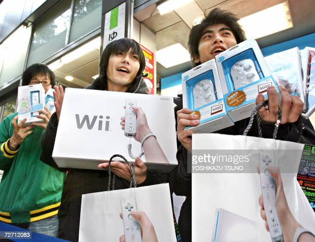 Japanese customers display Nintendo's new video game console 'Wii' they purchased at a Tokyo electric shop 02 December 2006 Thousands video game fans...