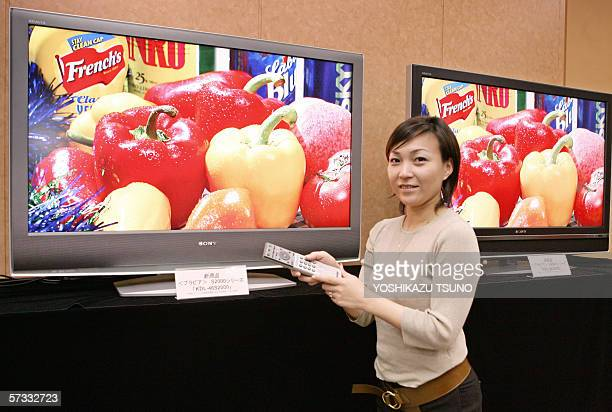 Japanese electronics gaint Sony employee Mina Naito displays the company's new LCD TV sets Bravia S and V series at their headquarters in Tokyo 13...