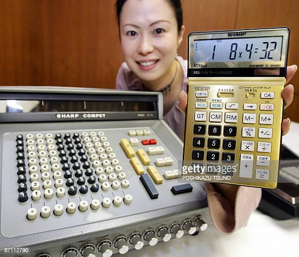 Japanese electronics giant Sharp employee Ema Tanaka displays a new gold colored electronic caluculator 'ELBN691' which is a commemoration model next...