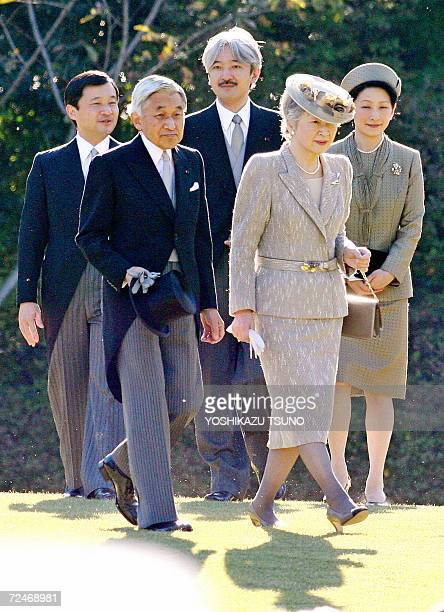 Japanese Emperor Akihito and Empress Michiko walk down a hill to greet guests at the annual autumn garden party in Tokyo, 09 November 2006, while...