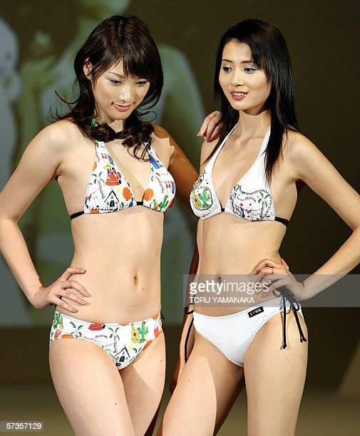 Japanese model Saki Akai and Chinese model Wang Yu pose as they display colorful printed bikinis during the 2006 swimwear show for Japanese...