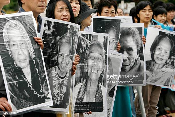Japanese women hold portraits of Chinese Philippine South Korean and Taiwanese former comfort women who were sex slaves for Japanese soldiers during...