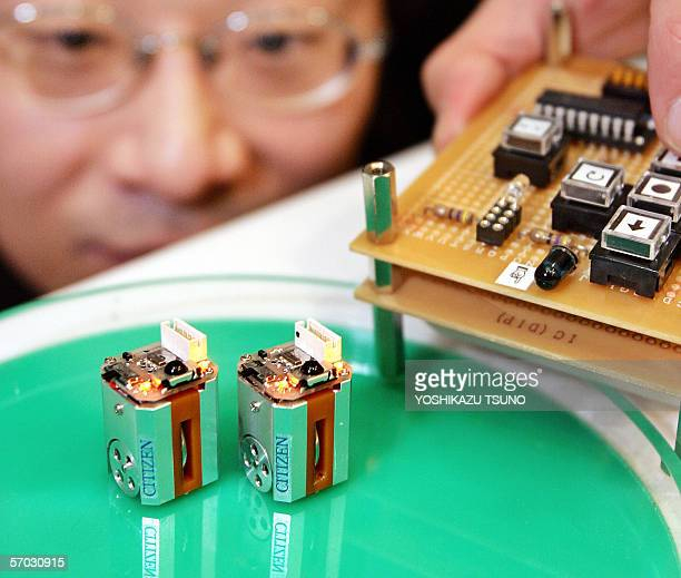 Japan's Citizen Watch engineer Yasuji Hirosawa displays the prototype model of thumb sized micro robot EcoBe equipped with two step motors to drive...