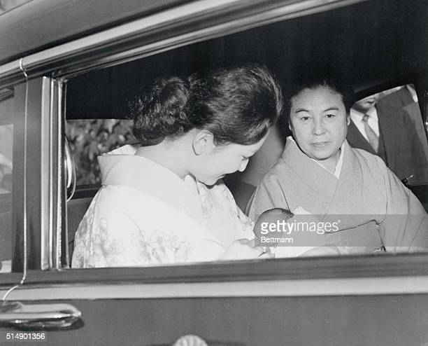 Japan's Crown Princess Michiko holds 18dayold Prince Naruhito in her arms as they leave the Imperial Household Hospital in an imperial car Sitting to...