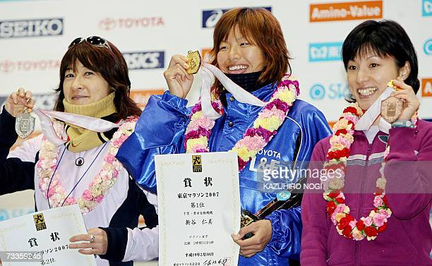Japan's Hitomi Niya winner of the women's category in the Tokyo Marathon shows her gold medal with other Japanese silver medallist Mari Tanigawa and...