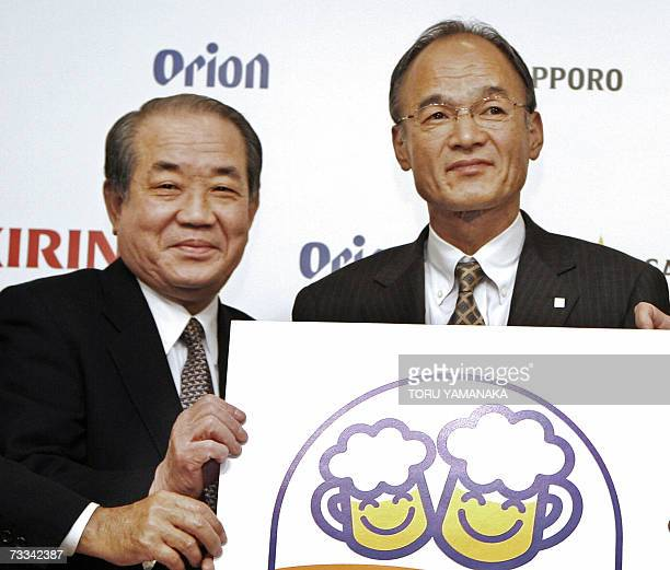 Japan's largest brewer Asahi Breweries President Hitoshi Ogida and Sapporo Holdings President Masaru Fukunaga smile as they shows a new signboard for...