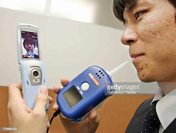 Japan's second largest mobile operator KDDI engineer Munezumi Wada demonstrates the alcohol tester 'AlcMobile' that will let bus and taxi companies...