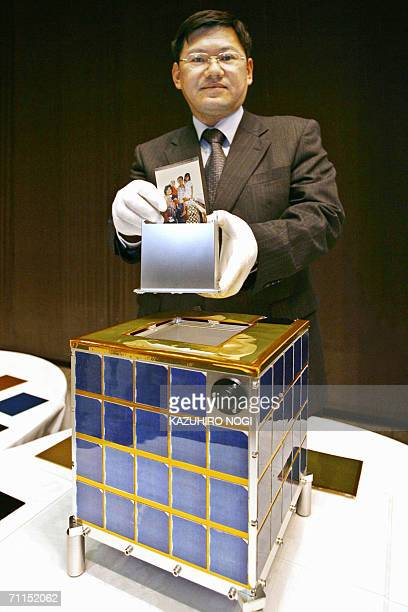 Japan's space development company Astro Research Corporation president Mitsuteru Sugiki displays a trial product of the satellite MySat1 and an...