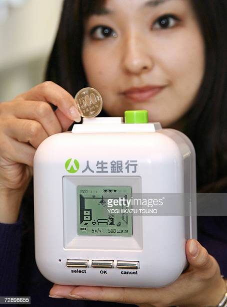 Japan's toy giant Tomy employee displays a cubic moneybox with LCD display 'Bank of Life' only for Japan's 500yen coin and to save up to 100000 yen...
