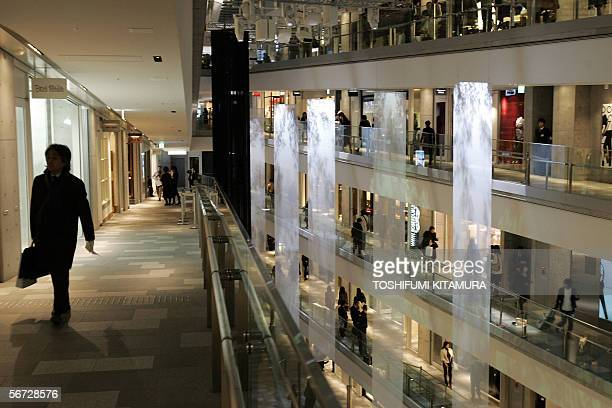 Journalists check fashionable shops inside the Omotesando Hills shopping mall and residential house during its press preview in Tokyo 02 February...