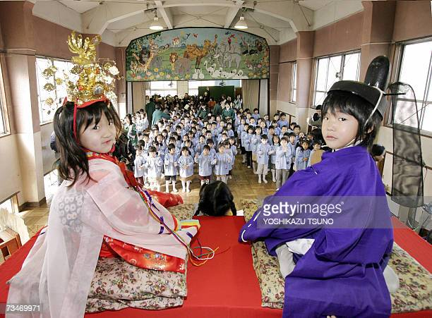 Kindergarten children Riko Miura and Haruto Miyamoto in traditional costumes pose on a platform in front of their classmates for hinamatsuri or doll...