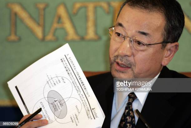 Livedoor president Kozo Hiramatsu shows off leaflets as he answers a question during his press conference at the Japan National Press Club in Tokyo...