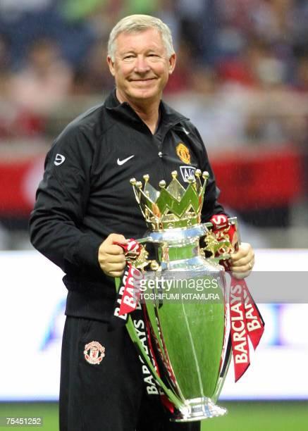 Manchester United head coach Alex Ferguson shows off the Premiership trophy prior to their friendly match against Urawa Reds in Saitama stadium in...