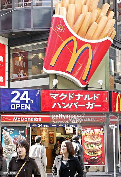 Pedestrians walk past a Mcdonald's outlet in Tokyo 08 February 2007 Japan's McDonald's Holdings announced the 2006 company net profit of 155 billion...