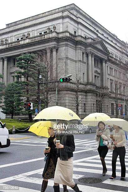 Pedestrians walk past the headquarters of the Bank of Japan in Tokyo, 20 February 2007. The Bank of Japan, still smarting from criticism it bowed to...