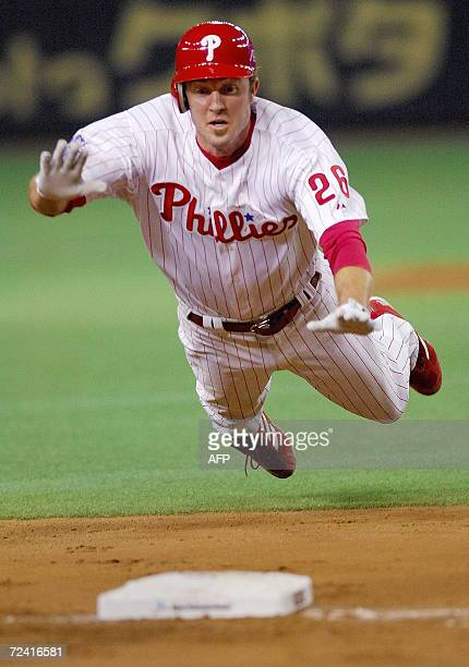 Philadelphia Phillies infielder Chase Utley jumps into the thirdbase when his teammate Ryan Howard hits a double in the sixth inning during the third...