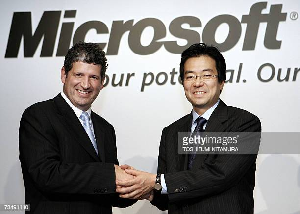 President of Microsoft KK the Japanese unit of the US computer giant Darren Huston shakes hands with the company's new Chief Operating Officer...