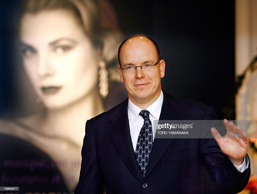 Prince Albert II of Monaco waves to people before a portrait of late his mother Princess Grace upon his arrival at 'La Princesse Grace de Monaco' exhibition in a Tokyo department store, 23 April 2007. Prince Albert is here on a three day visit to Japan. AFP PHOTO/Toru YAMANAKA