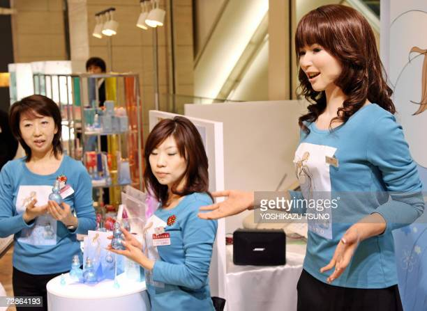 Promotional women along with a 165cm tall humanoid robot 'Actroid' introduce perfumes of French brand Azzaro at a Chiristmas gift promotion at...