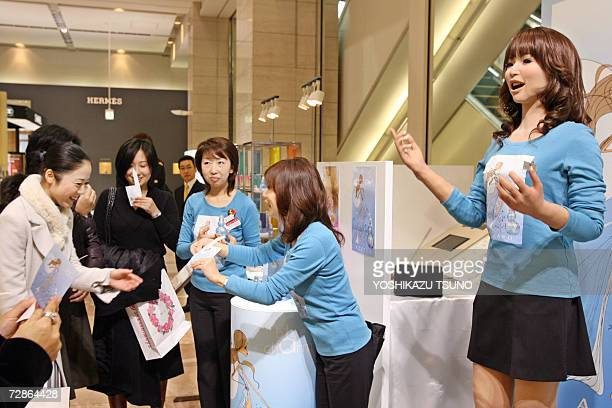 Promotional women along with a 165cm tall humanoid robot 'Actroid' introduce French Azzaro perfumes at a Chiristmas gift promotion at Takashimaya...