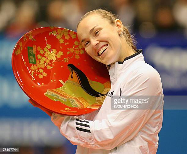 Switzerland's Martina Hingis presses her cheek with the winner's trophy during an awarding ceremony after the final match of the Pan Pacific Open...